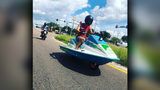 Man drives a Jet ski on the road