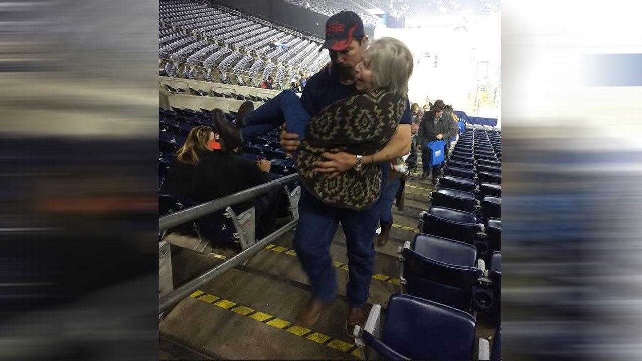 Good Samaritan carries woman having rough time walking upstairs at Houston Rodeo