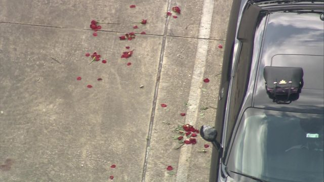 Roses scattered in parking lot of immigration office after domestic…