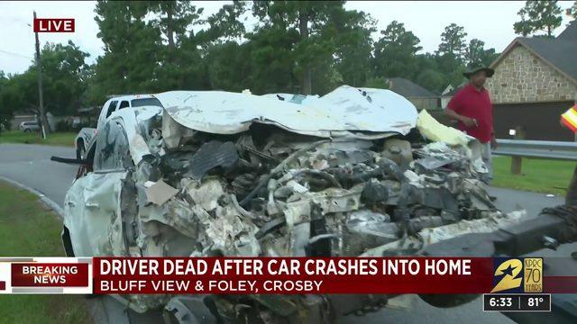 Man killed when car plows into home