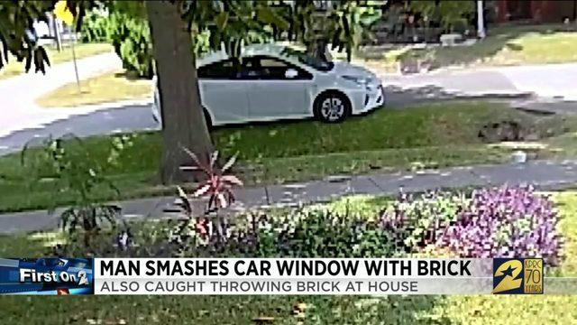 Man smashes car window with brick